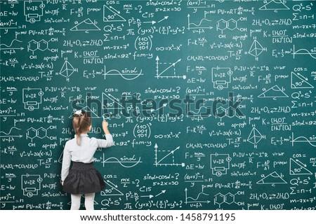 Schoolgirl writes on the blackboard formulas and mathematical equations