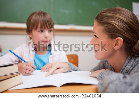 Schoolgirl writing a while her teacher is talking in a classroom