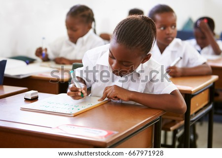Schoolgirl writing at her desk in elementary school lesson