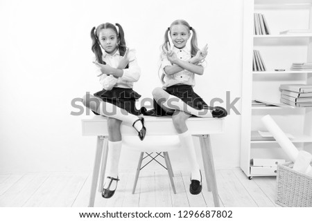 Schoolgirls cool confident faces with ponytails hairstyle. Best friends excellent pupils sit on desk with cool hands gesture. Popular pupil in class. Feel so confident and superior. School reputation. #1296687802