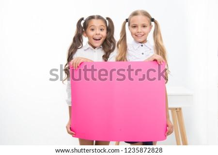 Schoolgirls hold advertisement poster copy space. Children hold advertising banner. Happy pupils children with blank paper for advertisement. School news concept. Your advertisement in good hands. #1235872828