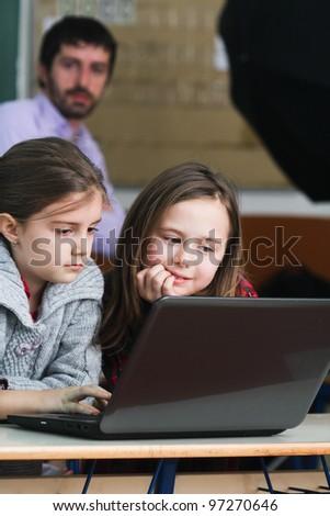 Schoolgirls working with laptop in classroom - stock photo