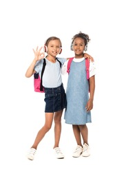 schoolkid listening music in wireless headphones, hugging african american friend and showing ok sign isolated on white