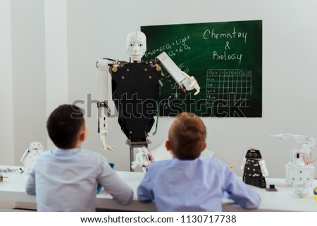 Schools of future. Smart self automated robot looking at the pupils while giving them a lesson #1130717738