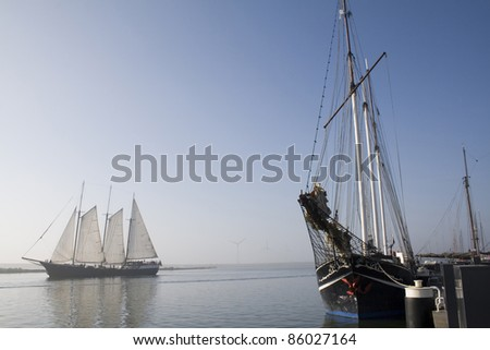 Schooner in the harbor of Enkhuizen with a three masted ship in the background