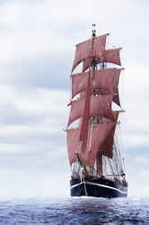 Schooner with beautiful red sails on the baltic sea.