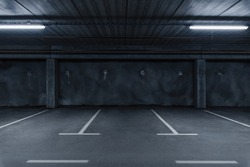 Sci fi looking dark and moody underground parking lot with fluorescent lights on.  Concrete wall