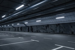 Sci fi looking dark and moody underground parking lot with fluorescent lights on.  Long hall