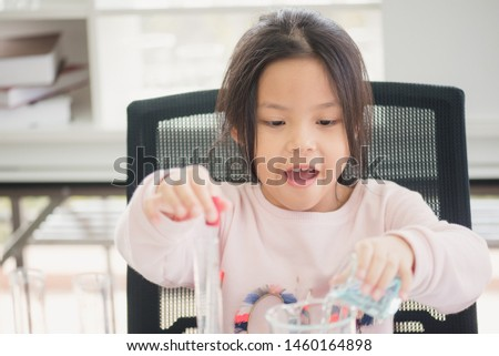 Science and education concept,Girl doing experiments in the laboratory.Little chemist holds scientific experiment