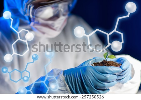 science, biology, ecology, research and people concept - close up of young scientist holding petri dish with plant and soil sample in bio laboratory over molecular structure