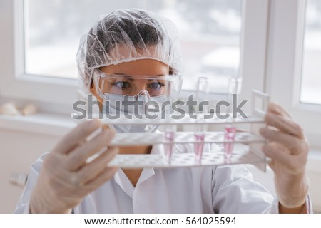 science, chemistry, technology, biology and people concept - young scientists with test tube making research in clinical laboratory #564025594