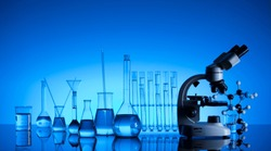 Science concept. Chemical experiment. Laboratory beakers, microscope, blue background.