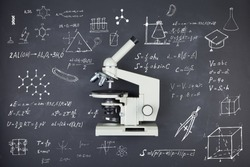 Science concept - microscope on the table in the auditorium, blackboard background