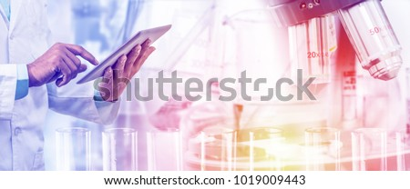 Science lab research and development concept - Scientist holding tablet computer with scientific instrument, microscope and chemical test tube in laboratory background.