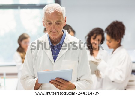 Science lecturer holding tablet pc in lab at the university