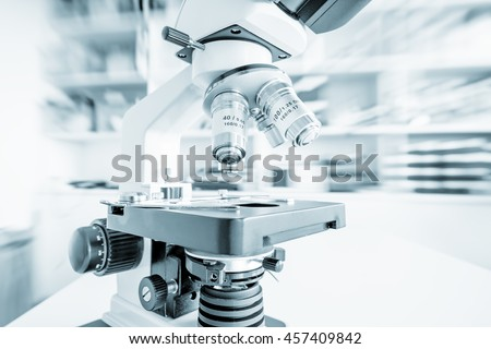 Science microscope on lab bench. Microbiology laboratory. Blue toned image of binocular microscope. Motion blur background