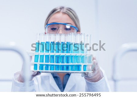 Science student holding tray of test tubes at the university