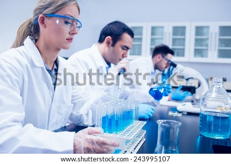 Science student using pipette in the lab to fill test tubes at the university