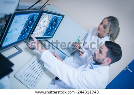 Science students looking at microscopic images at the university