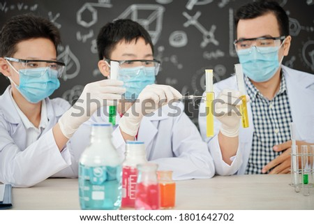 Science teacher and students in medical masks and rubber gloves holding tests-tubes with reagents and observing chemical reaction