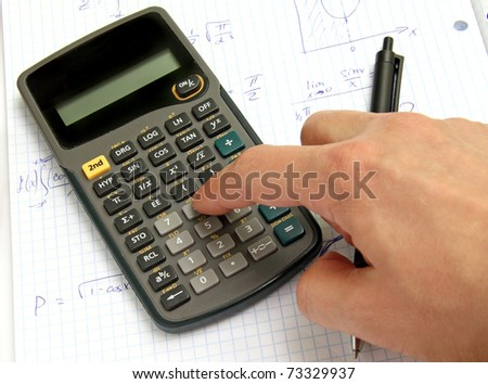 Scientific calculator on notebook paper and a hand