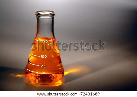 Scientific chemistry laboratory glass conical Erlenmeyer flask filled with gold amber color liquid for an experiment in a science research lab