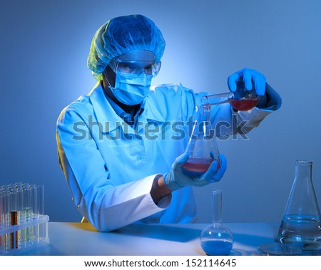 Scientific experiment. Confident young man in protective work wear making scientific experiment while isolated on white