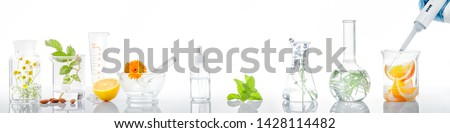 Scientific Experiment.Herbs,flower and orange  in test tubes Stockfoto ©