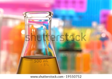 Scientific laboratory glass conical Erlenmeyer flask filled with amber chemical liquid for a chemistry experiment in a science research lab