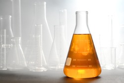 Scientific laboratory glass conical Erlenmeyer flask filled with amber orange chemical liquid with glassware equipment in fog or smoke for a chemistry experiment in a science research lab