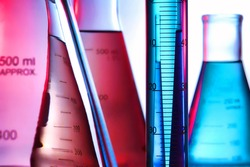 Scientific laboratory graduated cylinder filled with blue liquid and conical Erlenmeyer flasks full of aqua and pink chemical solution for an experiment in a science research lab