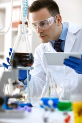 scientist analysis chemical experiment with tablet in modern laboratory