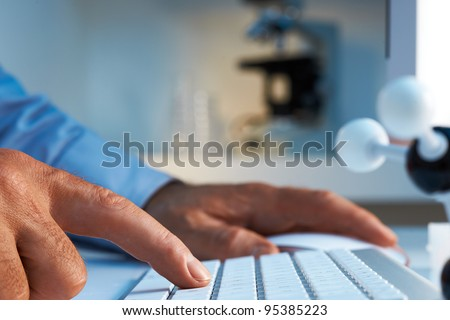 Scientist entering data into computer selective foucs - stock photo