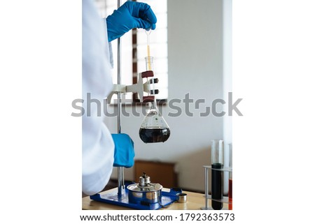 scientist examining chemical reagents in research center.Scientist in lab coat holding test tube with reagent, mixing reagents in glass flask, glassware containing chemical liquid, laboratory.