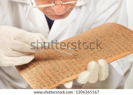 Scientist exploring ancient type of Akkad empire style cuneiform with tweezers