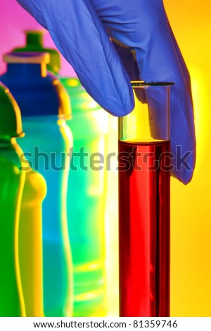 Scientist hand holding a laboratory glass test tube filled with red liquid solution next to colorful bottles for an experiment in a science research lab