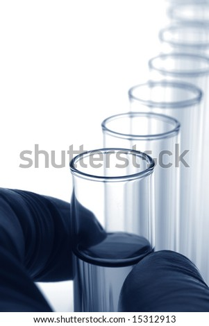 Scientist hand holding one of several  laboratory glass test tubes for an experiment in a science research lab