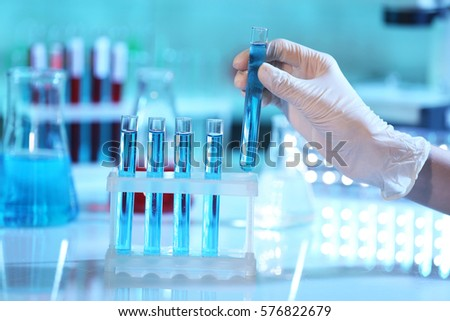 Scientist hand holding test tube in laboratory on blurred background