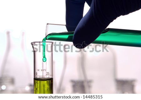 Scientist hand pouring a green chemical solution from a laboratory glass test tube into a scientific cylinder with yellow liquid for an experiment in a science research lab