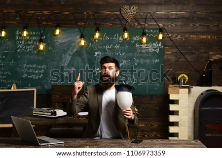 Scientist hipster with lightbulb on chalkboard. Bearded man hold bulb in classroom. Businessman in suit at school desk. Teacher with long beard on genius face. Got idea. enlightenment and invention.