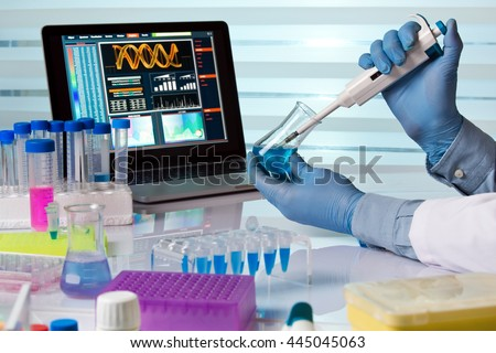scientist holding flask and working with laptop in lab / chemical engineer working in laboratory with pipette and flask