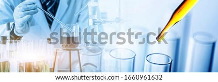 scientist holding flask with lab glassware and test tubes in chemical laboratory background, science laboratory research and development concept