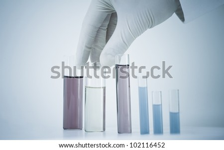 Scientist holding test tube in blue monochrome.