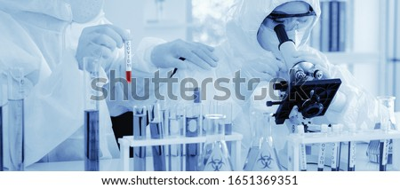 scientist in biohazard protection clothing analyzing covid 19 sample with microscope and holding coronavirus covid 19 blood sample tube on hand in laboratory, coronavirus covid 19 vaccine research