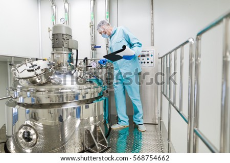 scientist in blue lab suit working with control panel, look at camera