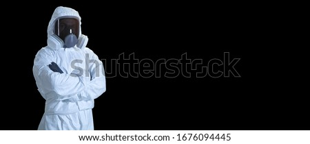 scientist in coronavirus protection suit. man in a protective suit and mask.  paramedic in full biosecurity suit isolated on black background. doctor in personal protective equipment suit