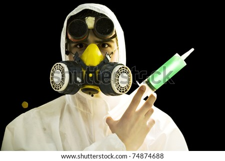 scientist in gas mask and goggles holding syringe with green substance