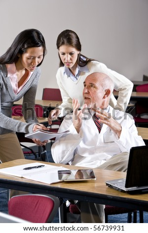 Scientist in lab coat talking to assistants in conference room