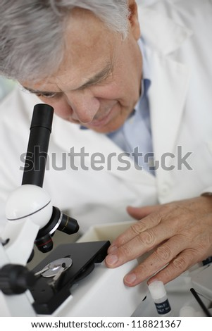 Scientist in lab looking through microscope lens - stock photo