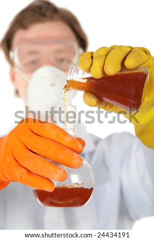 Scientist in respirator and rubber gloves pours  brown liquid from one flask in another
